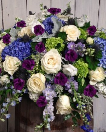 Sympathy & Funeral Flowers: The Amethyst Blanket is our signature blanket arrangement of roses, hydrangea and delphinium accented with seasonal foliage.