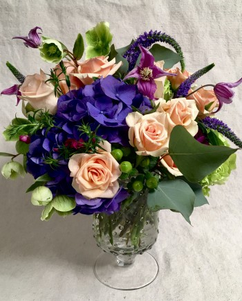Flowers Online: Our Lydia arrangement includes dutch hydrangea surrounded with soft peach roses and other garden favorites in a hobnail vase.
