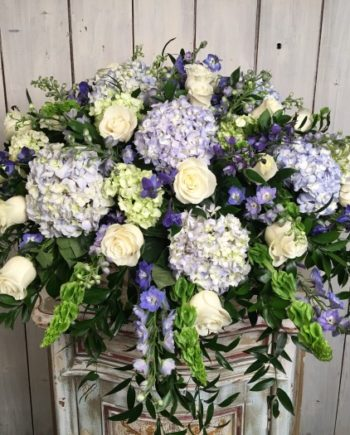 Sympathy & Funeral Flowers: The Oceanview Blanket features cascading hybrid blue and white blooms with textured seasonal greenery.