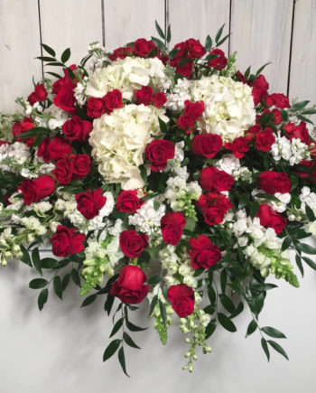 A stately sympathy blanket of red roses accompanied by a selection of premium white blooms.