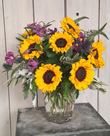 Vibrant sunflowers styled with thistle, clematis and other premium blooms and greens.