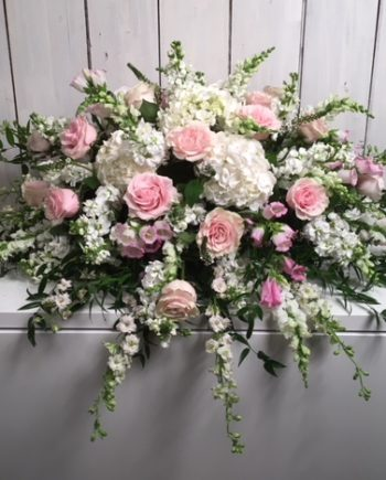Sympathy & Funeral Flowers: A subtle blanket of calming white hydrangea, pink roses and other blooms accented with seasonal textured foliage.